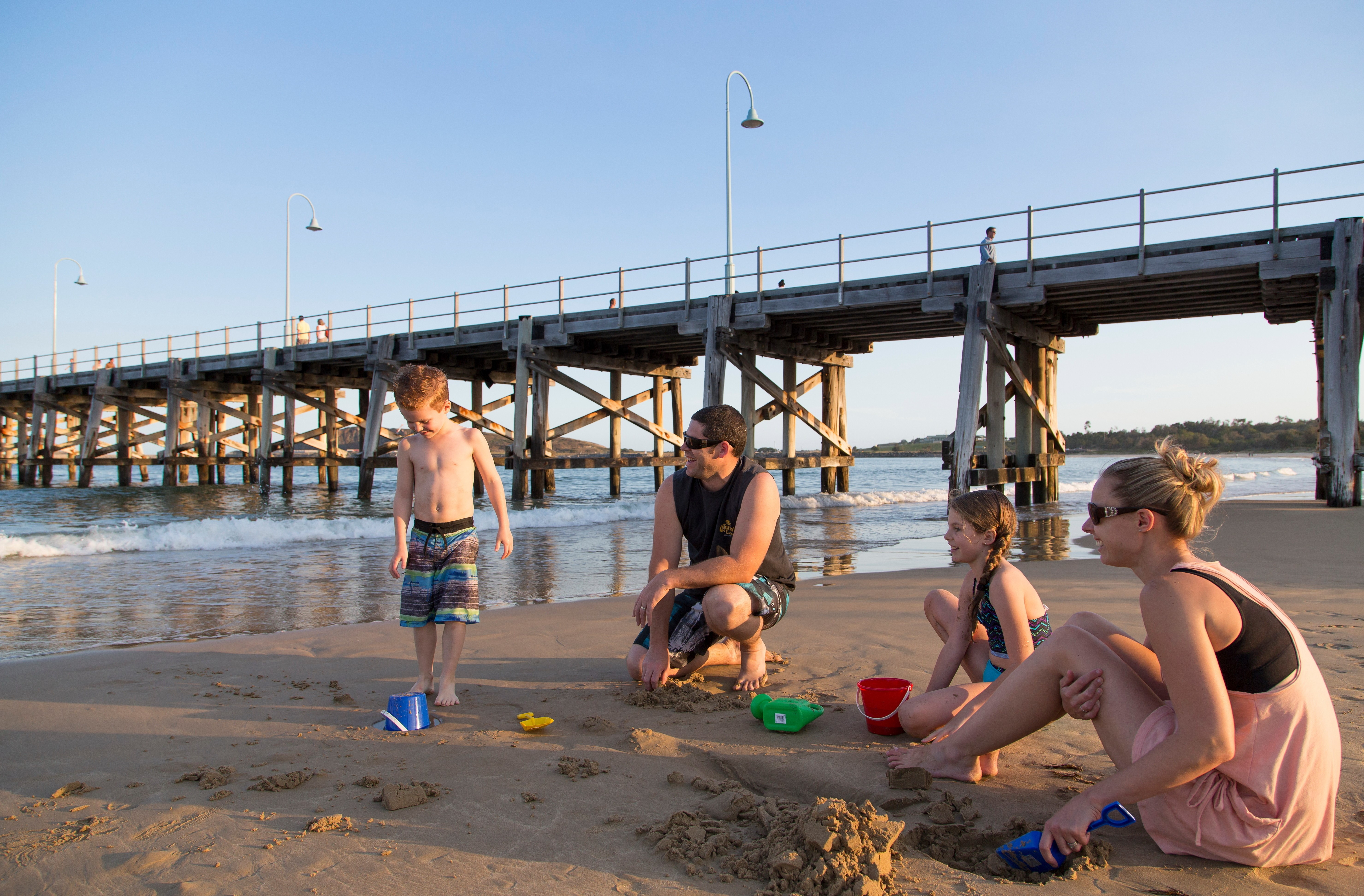 Image of a family playing on the beach at Coffs Harbour jetty