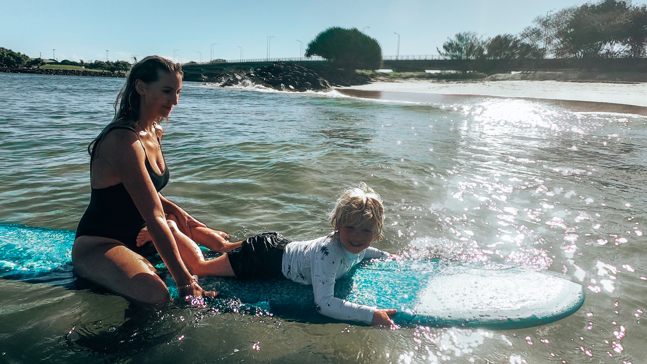 Image of a woman and son standup paddleboarding at Reflections Holiday Parks Jimmys Beach