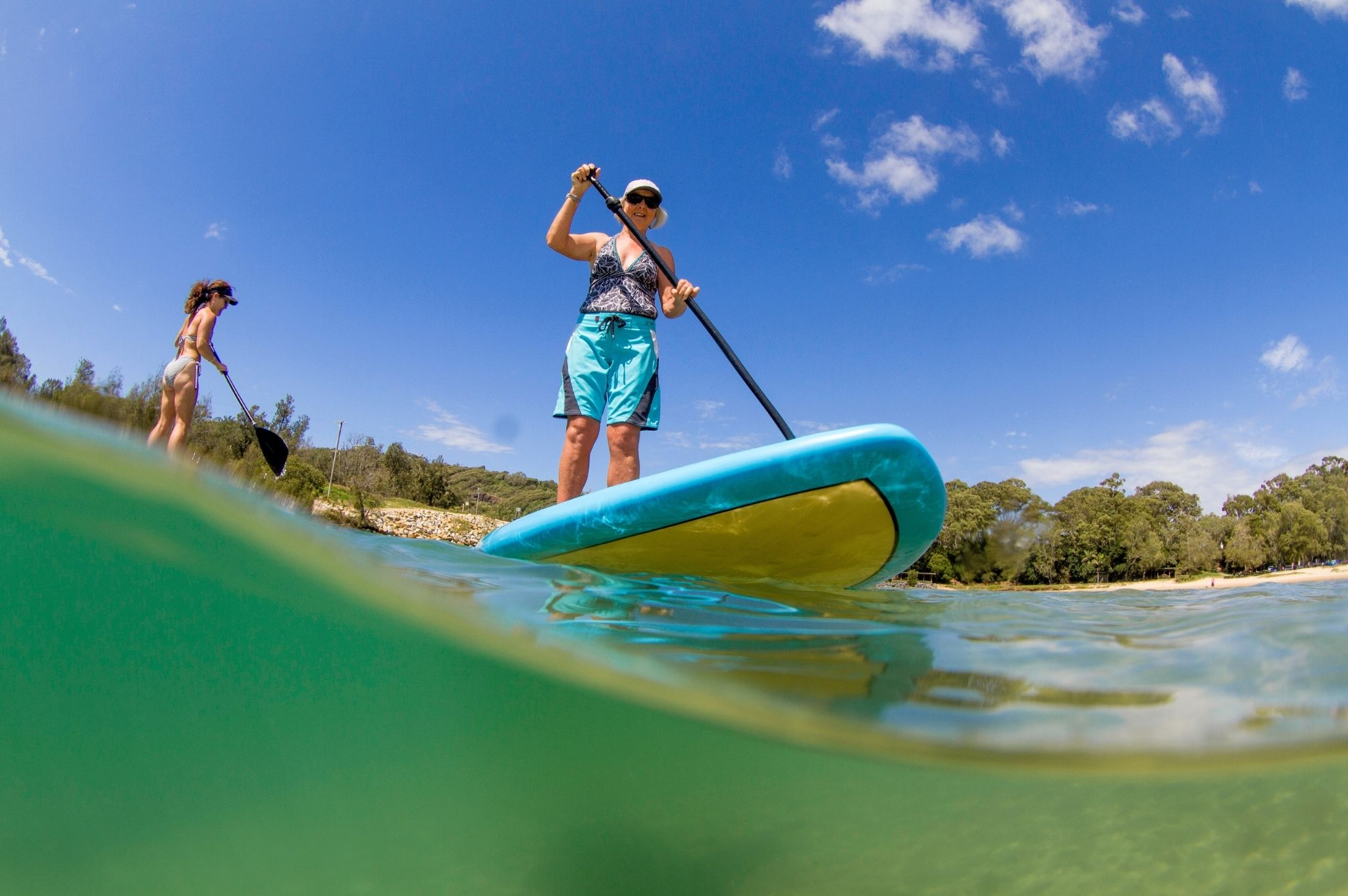 Image of a woman standup paddleboarding at Reflections Boambee Creek Reserve