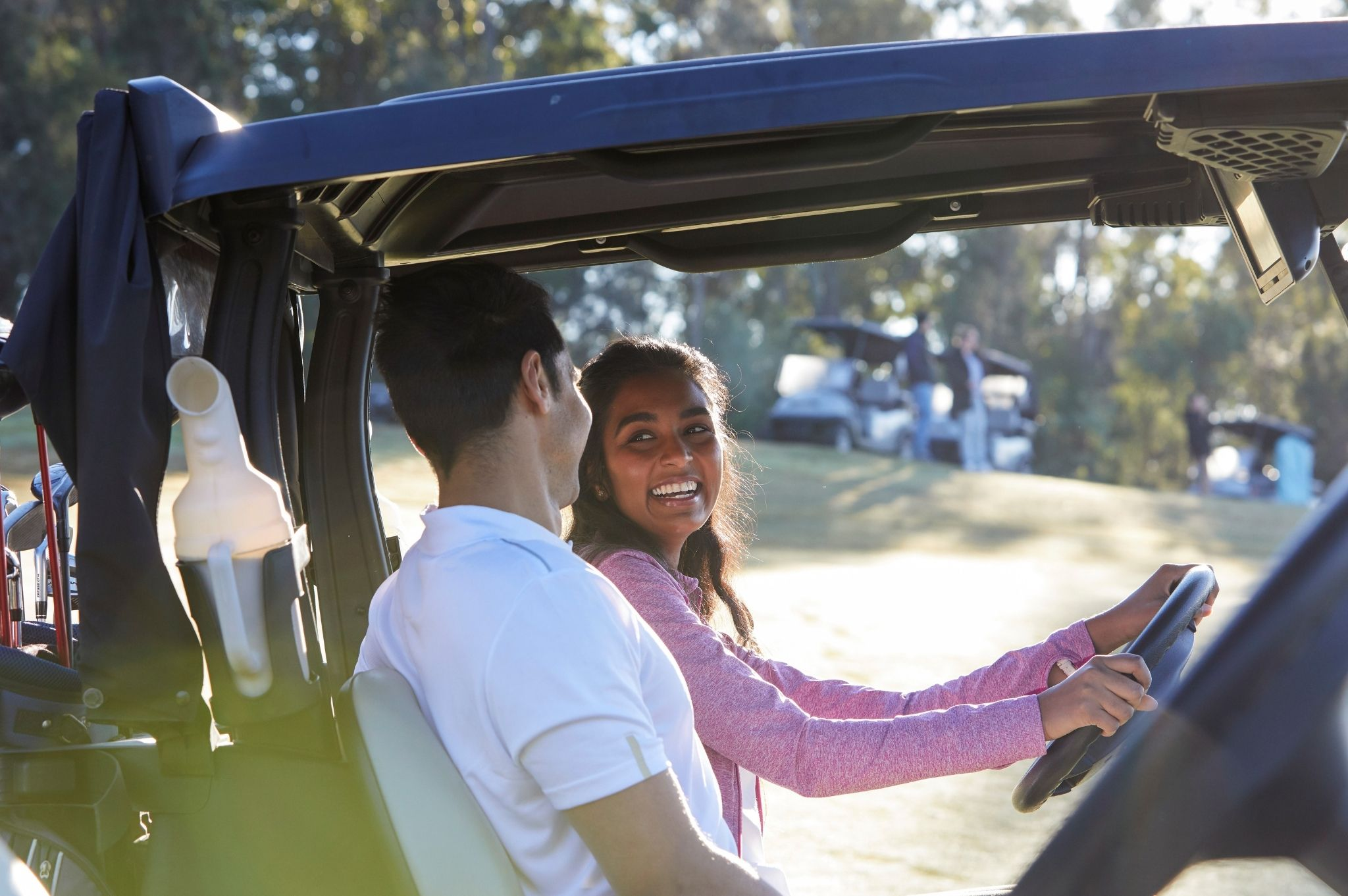 Image of a couple driving a golf cart on a NSW golf course