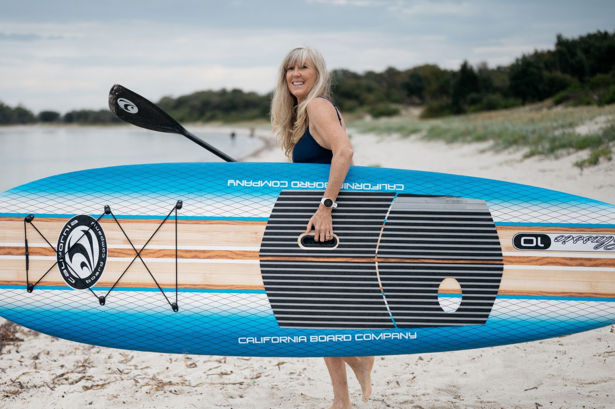Image of a woman on the beach with her standup paddleboard at Reflections Holiday Parks Jimmys Beach