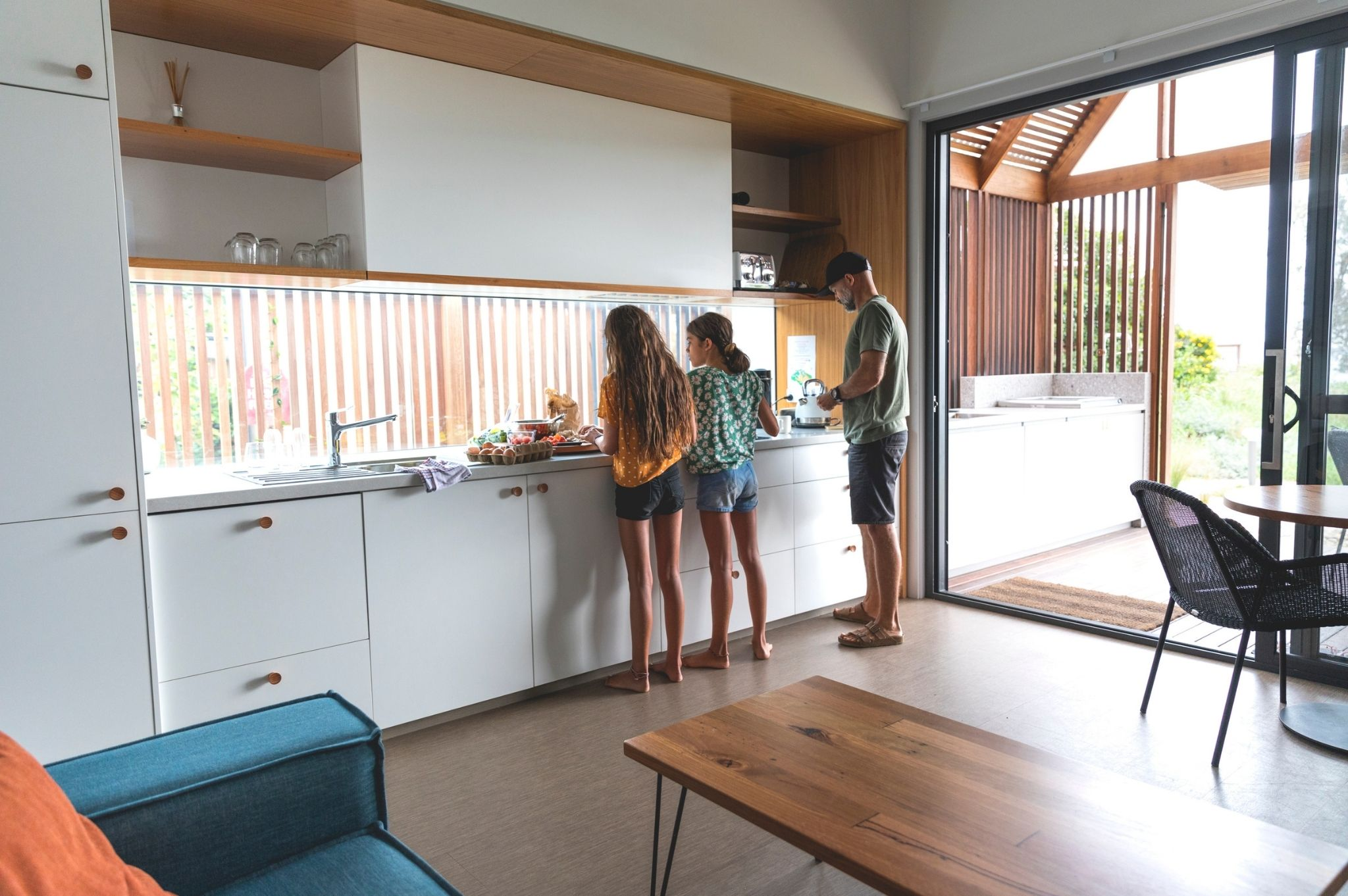 Image of a family cooking in their cabin kitchen at Reflections Holiday Parks Seal Rocks