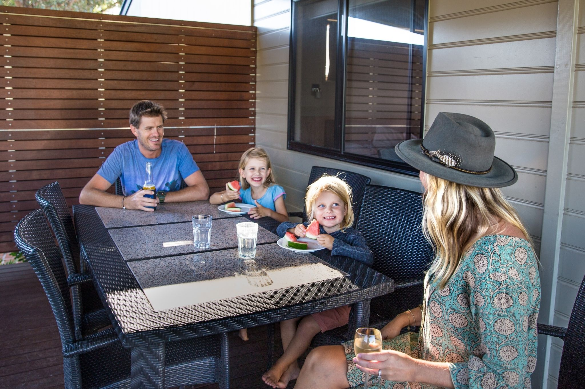 Image of a family eating together on their cabin balcony at Reflections Holiday Parks Hawks Nest