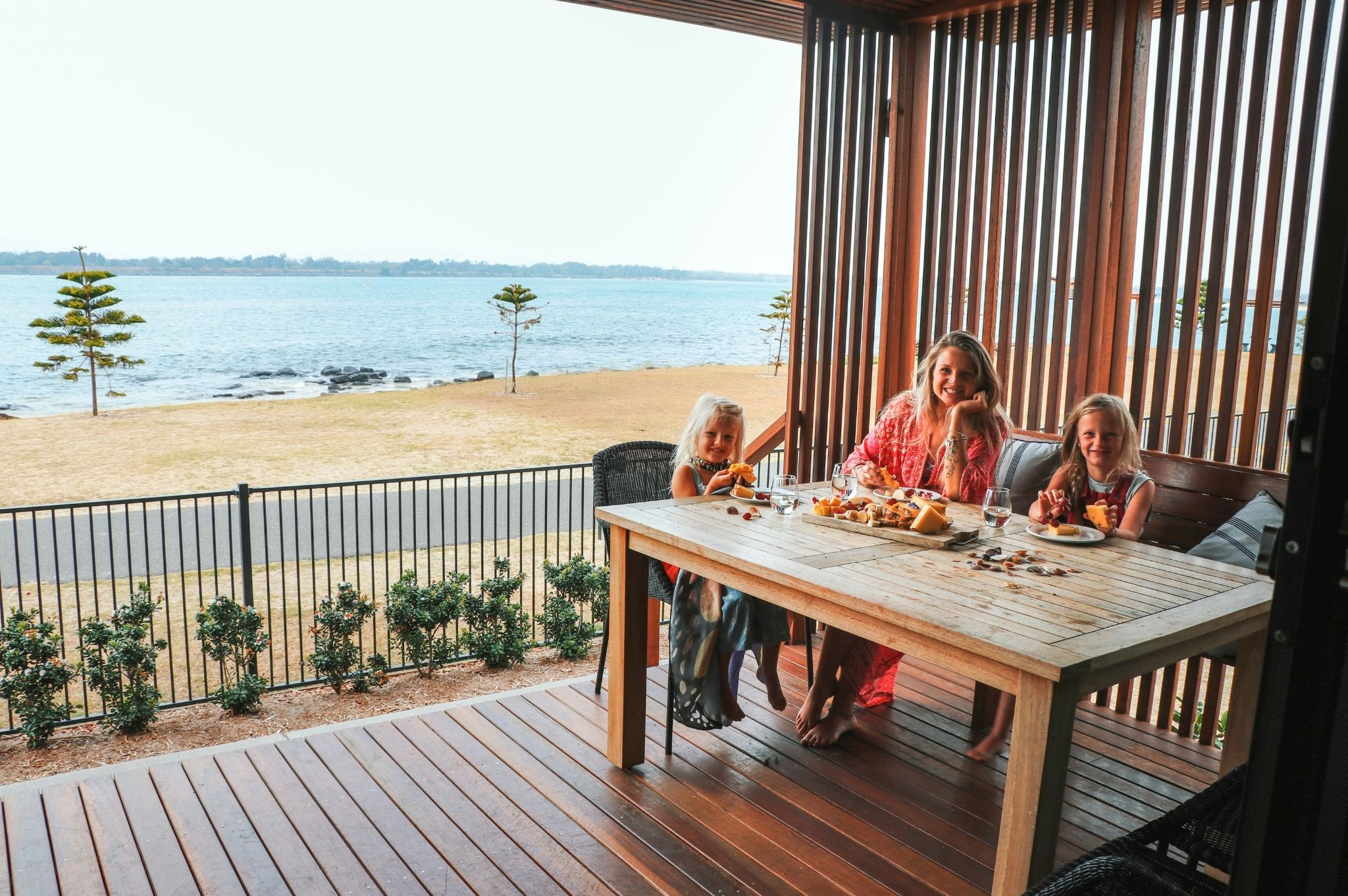 Image of a family eating breakfast on their cabin balcony at Reflections Holiday Parks Shaws Bay