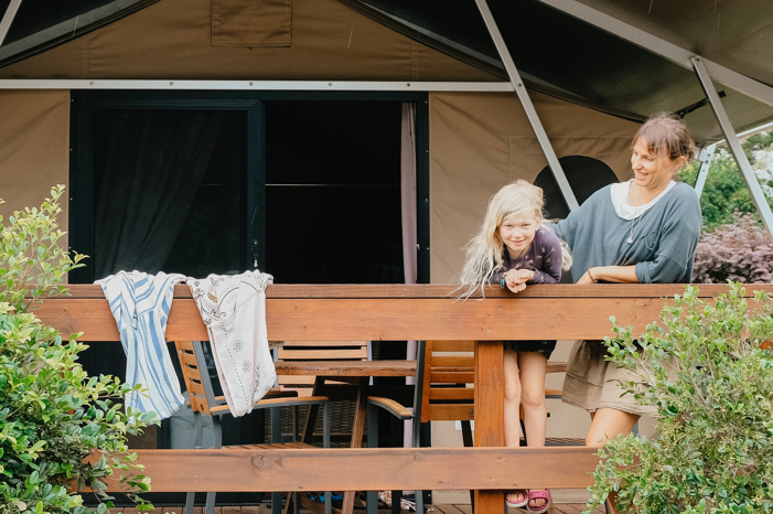 Image of a woman and child on beach tent balcony at Reflections Holiday ParksMylestom