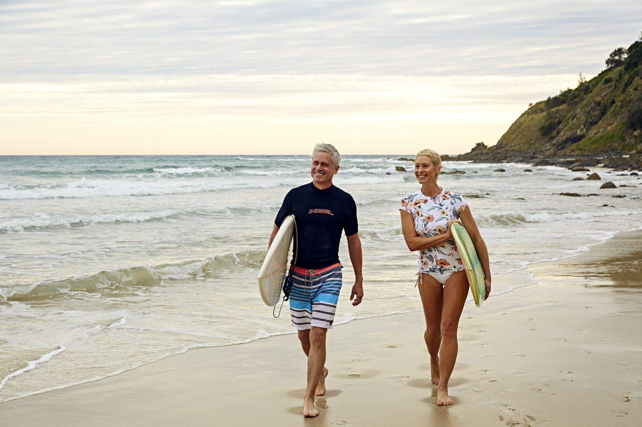 Image of a couple with surfboards at Wategos Beach in Byron Bay NSW