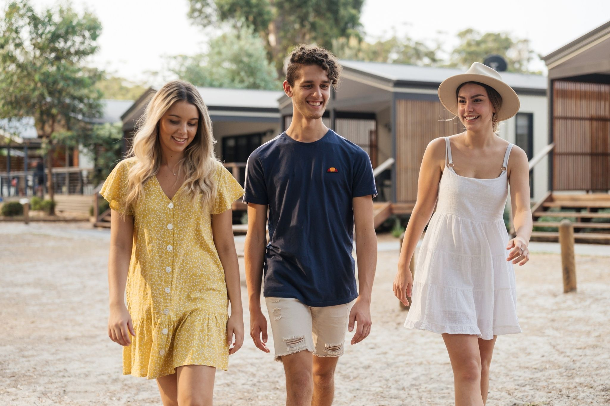 Image of three people walking in front of cabins at Reflections Holiday Parks Jimmys Beach
