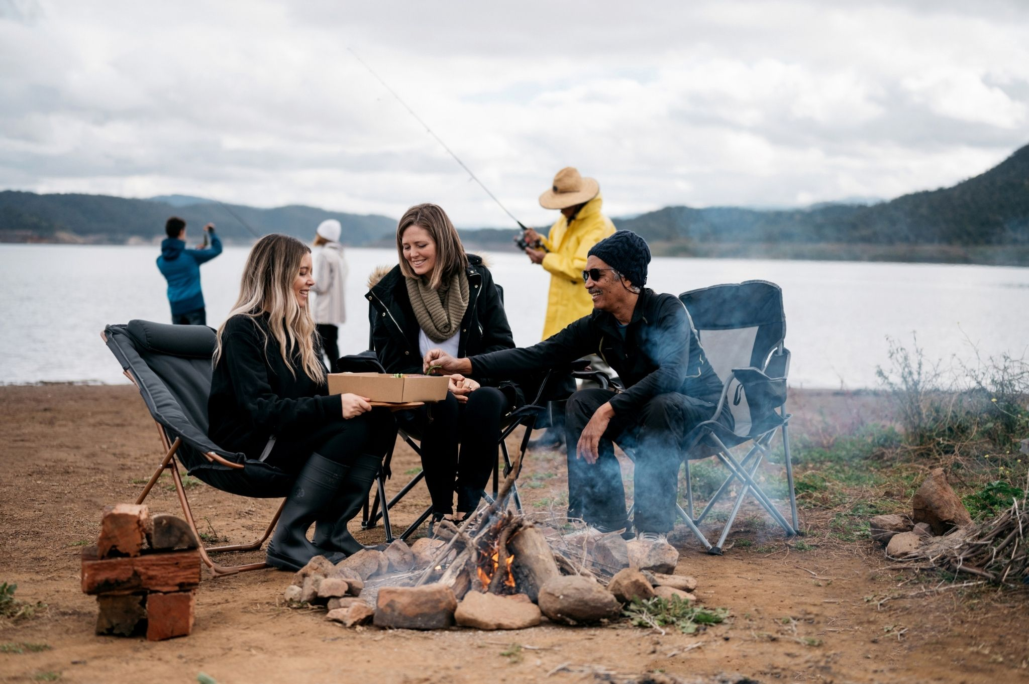 Image of a family eating by a campfire at Reflections Holiday Parks Lake Glenbawn