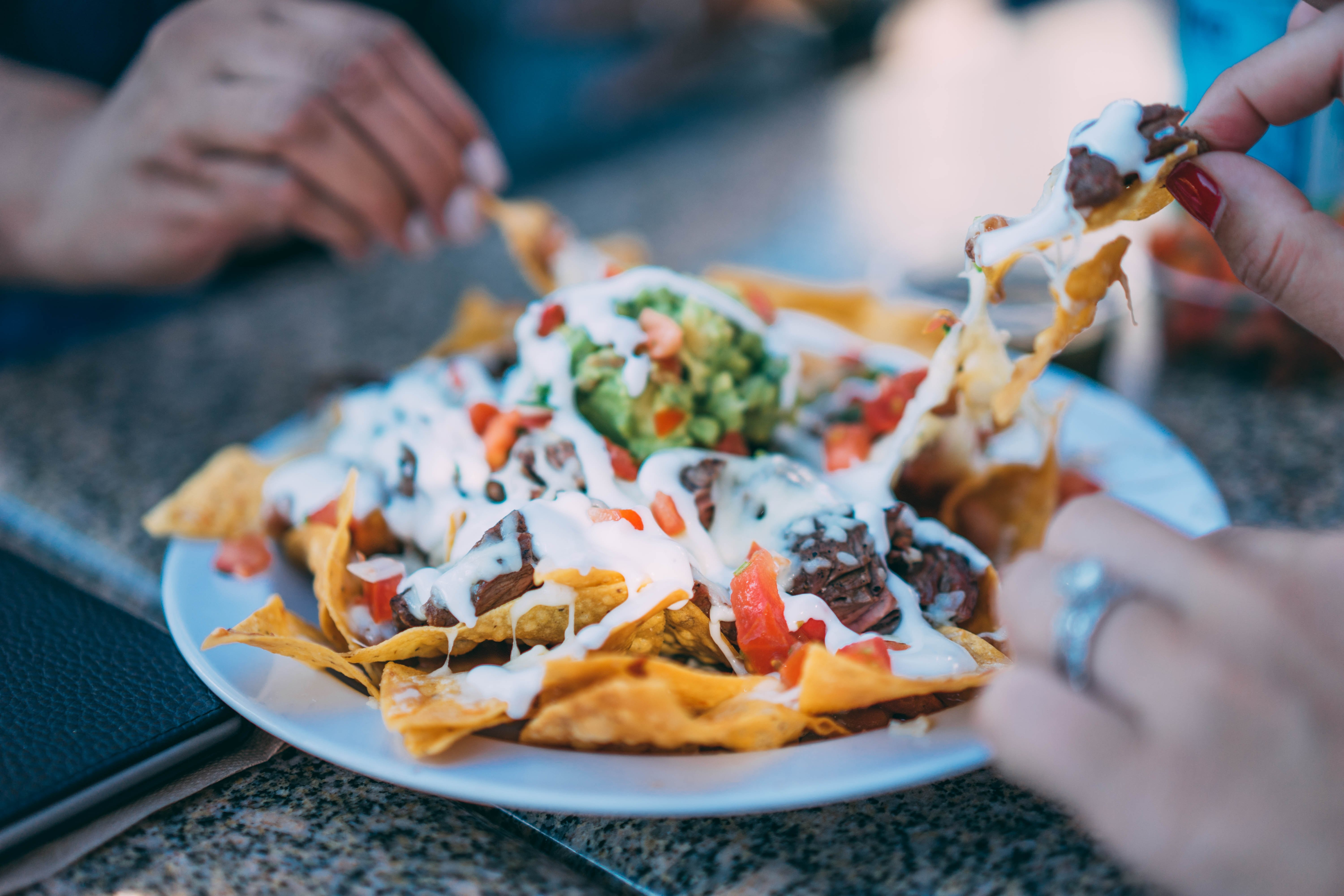 Image of people eating a plate of nachos